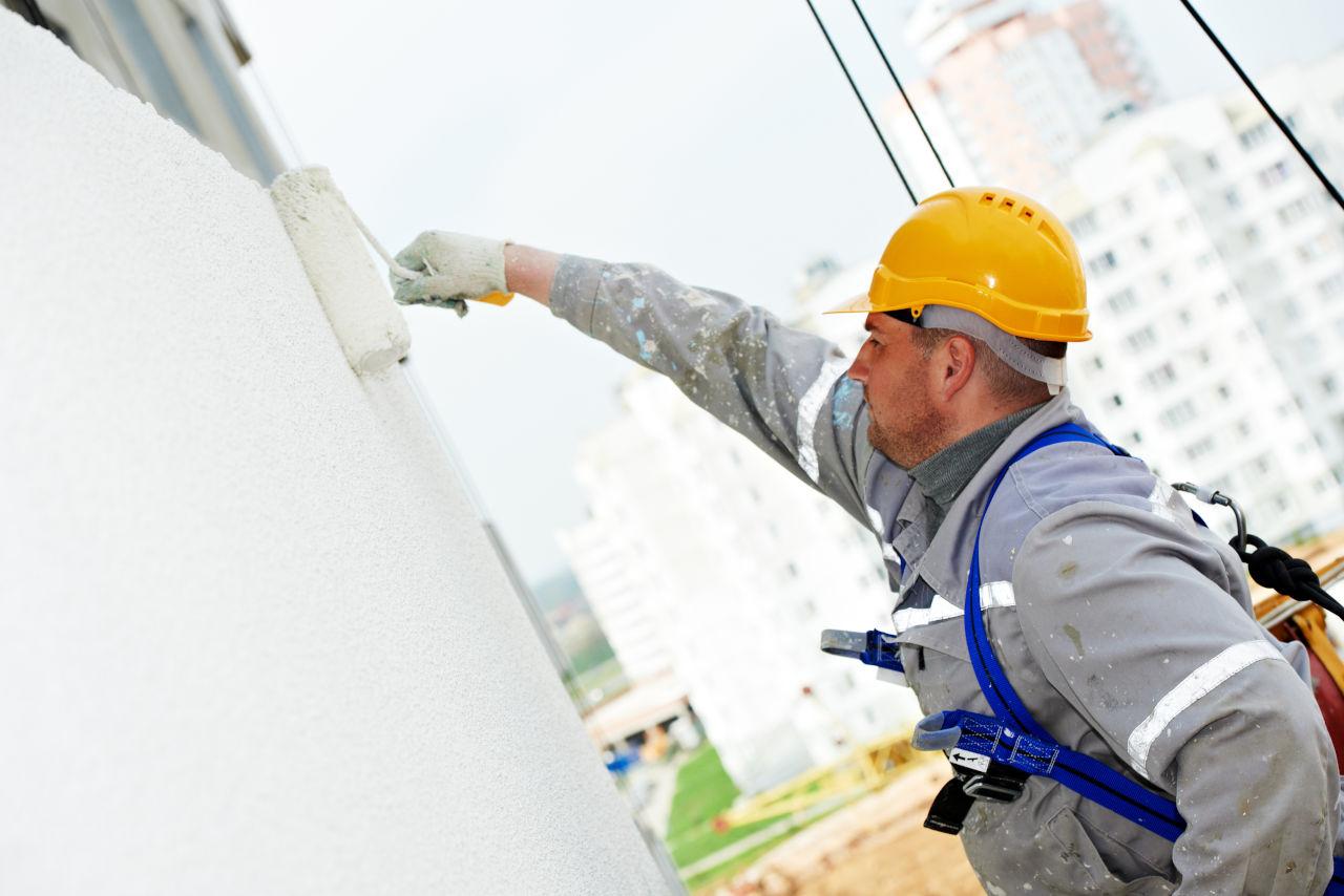 Operario pintando la facha exterior de un edificio con rodillo